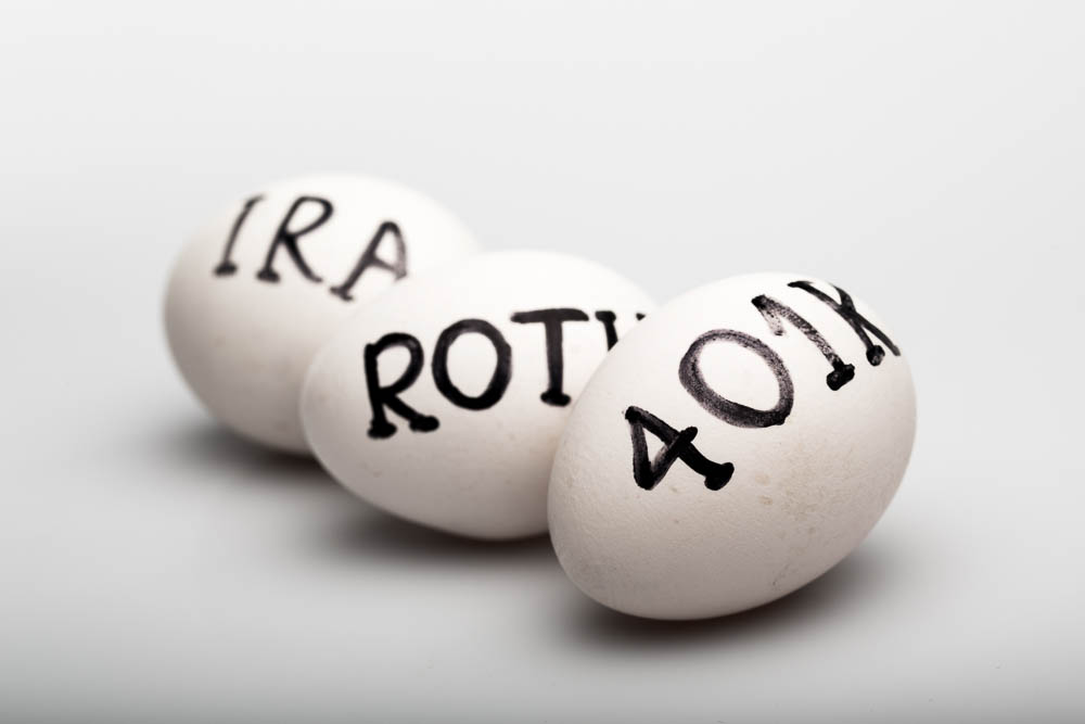 """Three Eggs with the Inscription """"Ira Roth 401K"""" on Grey Background"""